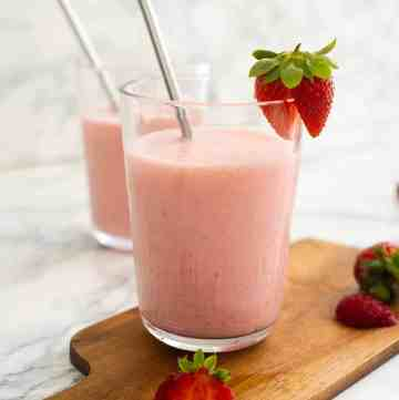 Strawberry lassi in a glass with a steel straw
