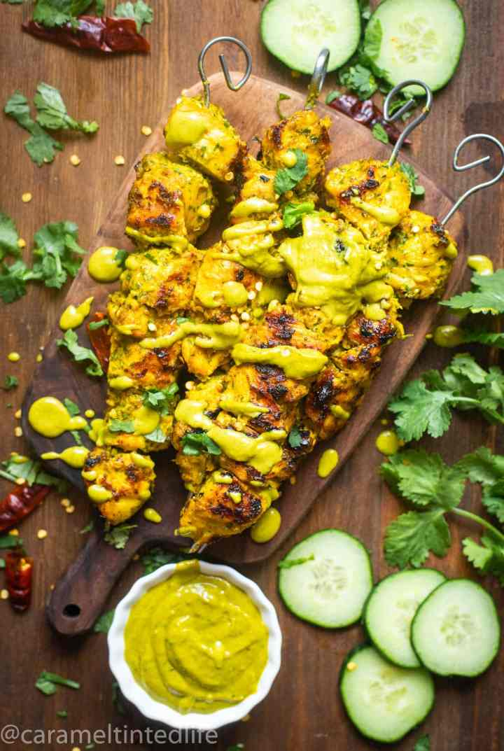 Chicken satay on a wooded board with peanut dipping sauce
