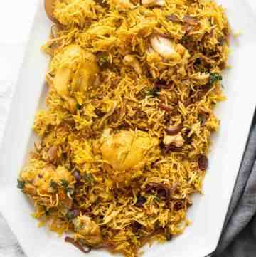 Chicken biryani served on a white tray with a spoon