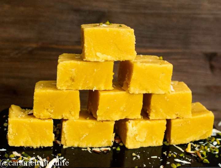 Mysore pak pices stack like a bricks on a black baking tin, against a wooden backdrop