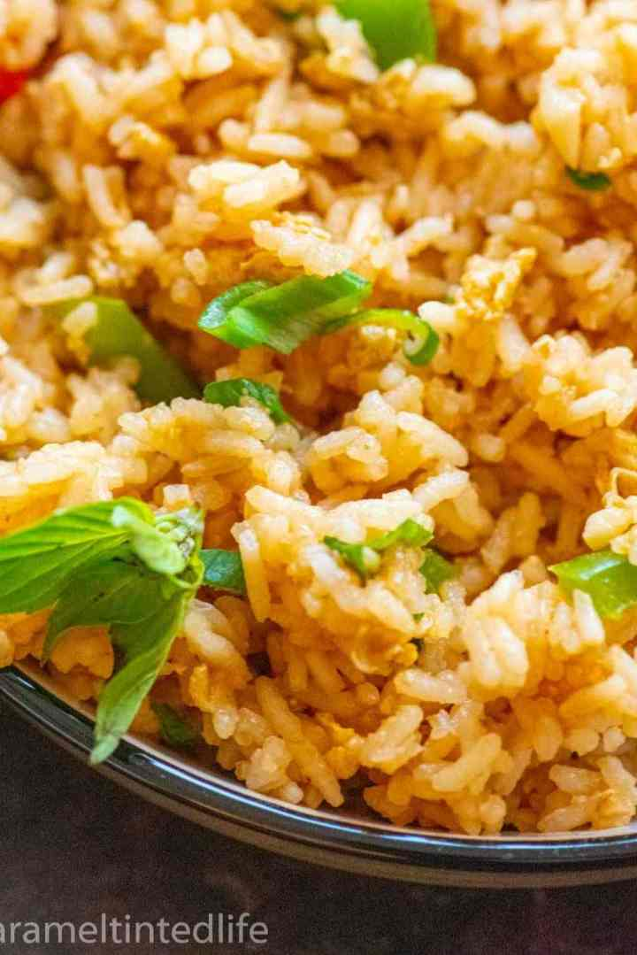 Closeup of fried rice in a bowl, garnished with a basil leaf cluster and green onions