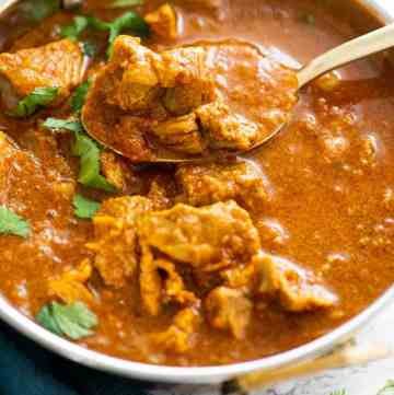 Spoon holding lamb curry over a bowl