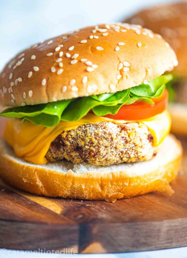 a Close up of a chicken burger on a wooden surface