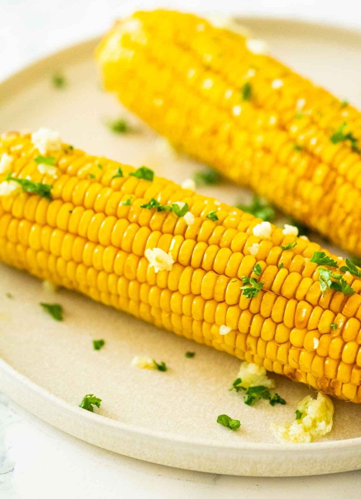 side view of corn on the cob on a cream plate