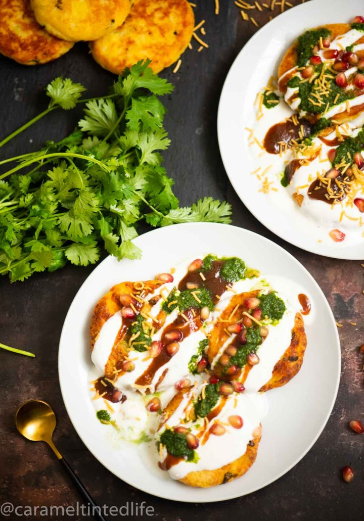 two plates of aloo tikki chaat, cilantro, and a spoon on a brown backdrop
