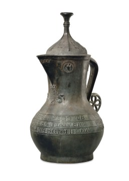 The Asante Jug (Richard II Ewer). Manufactured in England, 1390–99; found at Manhyia Palace, Kumase, Asante region, Ghana. Copper alloy. The British Museum, London, England, 1896,0727.1 This ewer, which was made in England in the 14th century, was taken by the British from Kumase, the capital of the Asante Kingdom, during the Anglo-Asante War of 1896. It is embellished with heraldic motifs and Lombardic inscriptions. The royal arms of England on the front of the jug reference the reigns of both Edward III and Richard II, but the badges on the lid depicting a stag indicate that it was produced during Richard's reign, specifically between 1390 and 1400. The ewer might have traveled across Saharan trade routes soon after it was made, or it might have been imported to Asante at a later time through trade along the Atlantic coast.