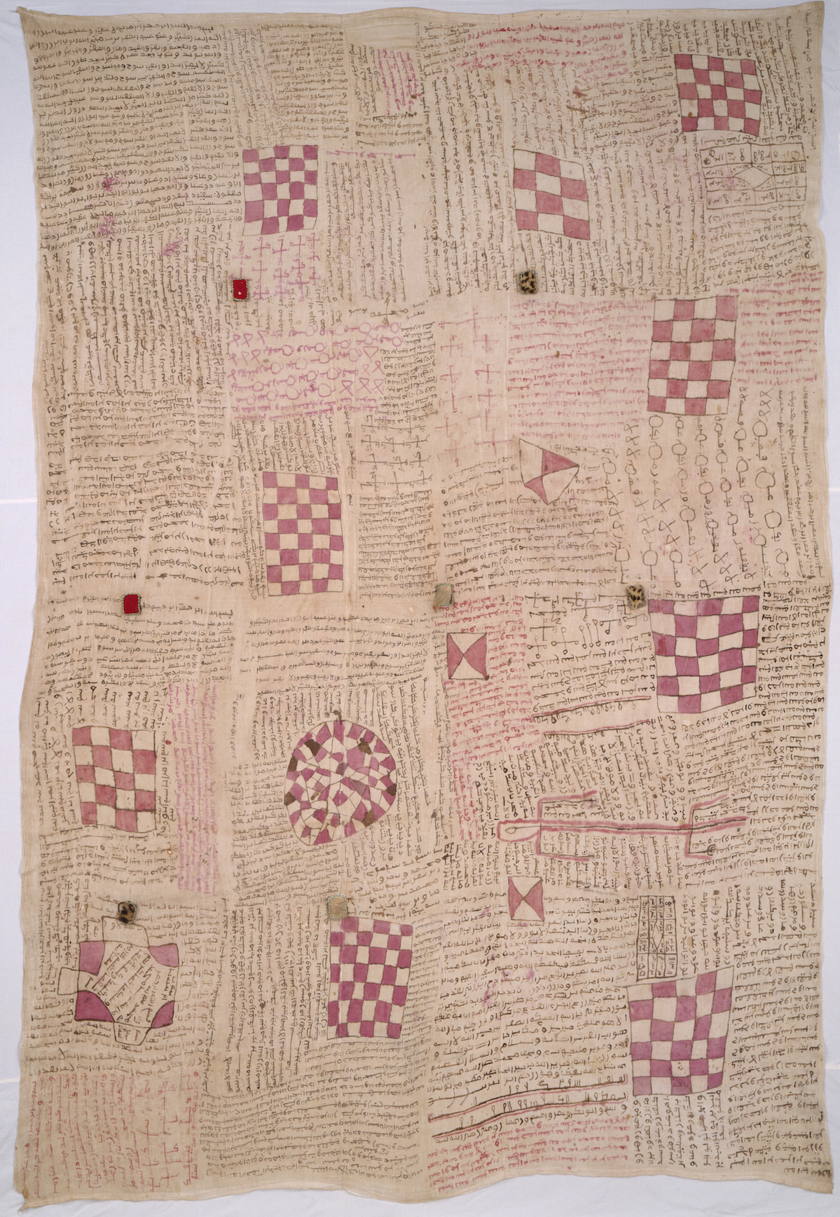 Talismanic textile, probably Senegal, late 19th or early 20th century. Cotton, plain woven panels (4) joined and painted, with amulets of animal hide and felt attached by knotted leather strips, 255.2 x 178.8 cm. Art Institute of Chicago, African and Amerindian Purchase Endowment, 2000.326. Photograph courtesy of The Art Institute of Chicago/Art Resource, NY The Qur'anic passages written across this textile and contained in the amulets attached to it have therapeutic intent. Leather-encased amulets are also worn on the body in the form of necklaces and other items of adornment. The activation of the words of the Qur'an for protection and healing is a widespread Islamic practice.