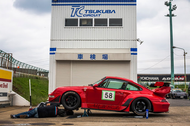 "RWB Porsche nicknamed ""Abfall Seele"" in red with the front end lifted by jack and mechanic working below the car at Tsukuba Circuit, Japan"