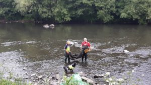 Two volunteers removing rubbish from the Taff