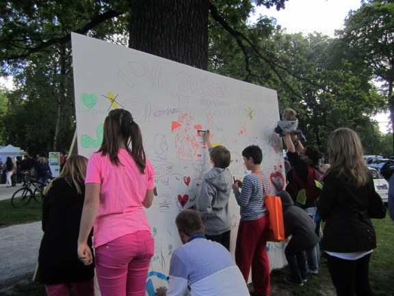 Optimistic kids & adults trying to stop nuclear weapons by making a poster.