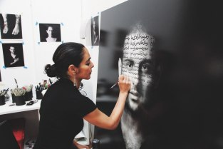 Shirin Neshat writing Persian poetry on the image of a young Iranian.