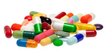 A close-up of a pile of colorful pills and capsules.