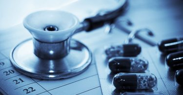 Stethoscope and pills over notebook blue toned