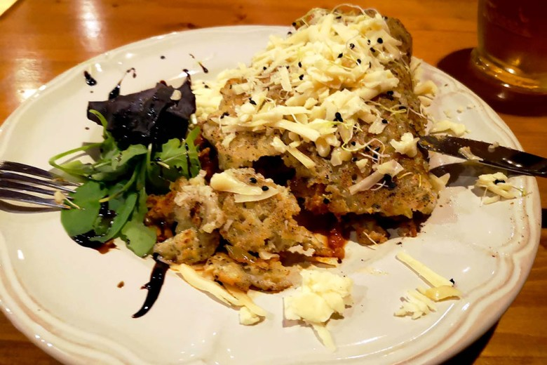 Pork stew wrapped in potato pancakes and topped with cheese is a tasty and filling meal