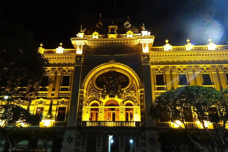 Sucre's landmark buildings are lit up at night, illuminating their white and golden features