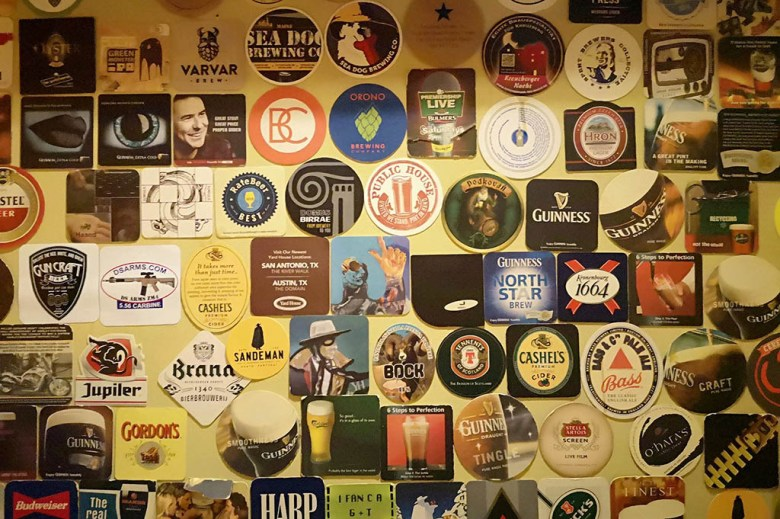 The beer-mat-covered walls of Baras Šuo, one of the best bars in Vilnius for craft beer