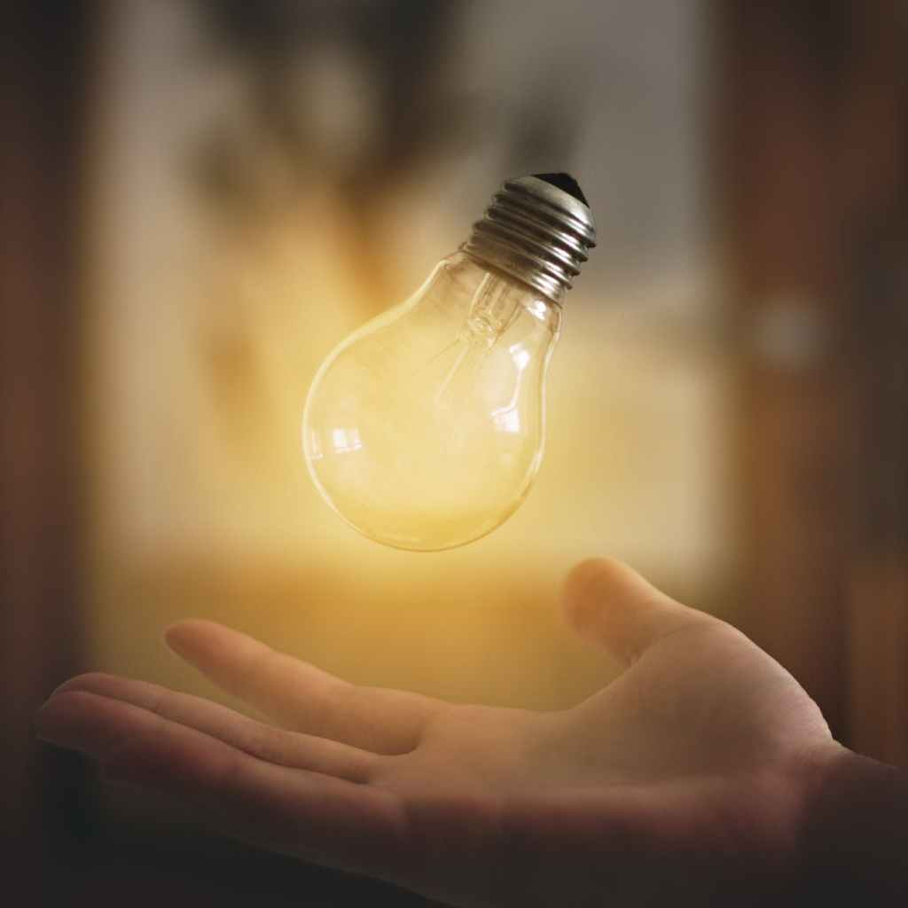 light bulb floating above person s hand