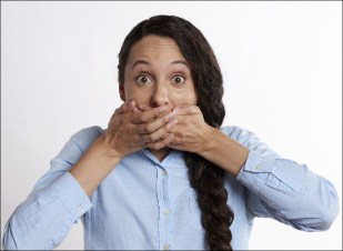 Woman appearing shocked, with her hands over her mouth.