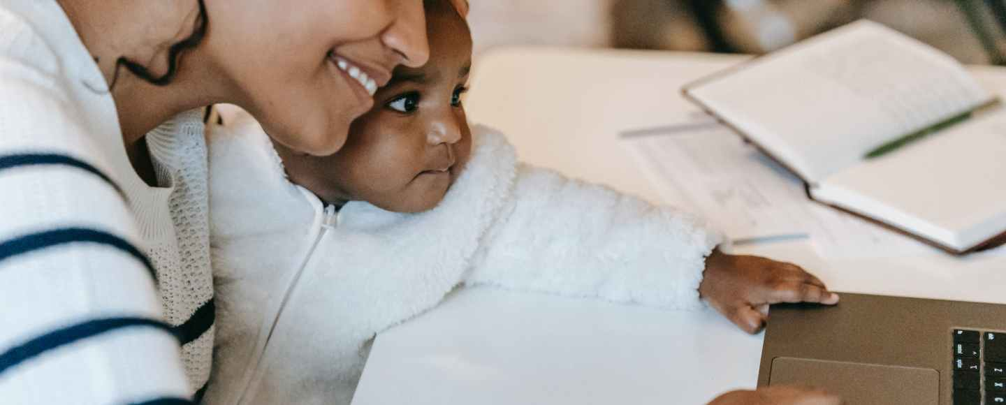 smiling young ethnic woman working remotely on laptop with cute baby on knees