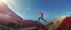 A man jumping from one boulder to another boulder while hiking in the United States