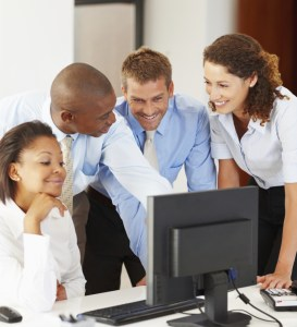 Business colleagues using computer and discussing project