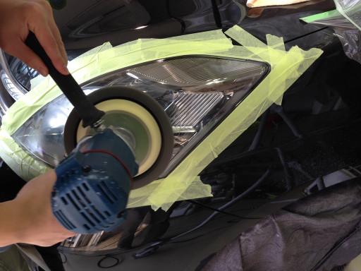 TOYOTA ISIS 黒のヘッドライトにヘッドライト研磨を施工しているところ