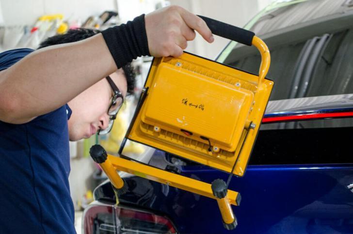 ディープブルーメタリックのTesla Model Xのリアに小型ライトをかざしてボディの状態を確認しているところ