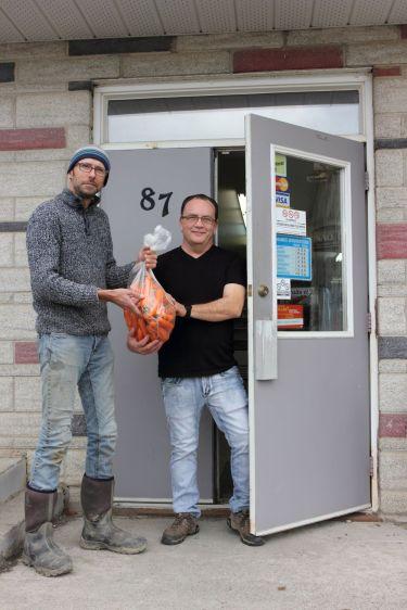 Donald livre un sac de carottes à Robin, propriétaire de l'épicerie.