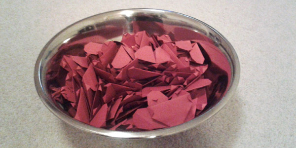 A Stainless Steel Bowl filled with paper hearts.