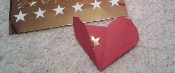 Origami heart with gold star sticker inside.
