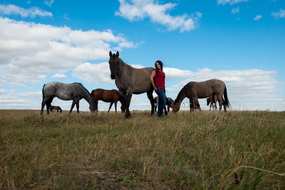 Women with her horses in an Alberta prairie field