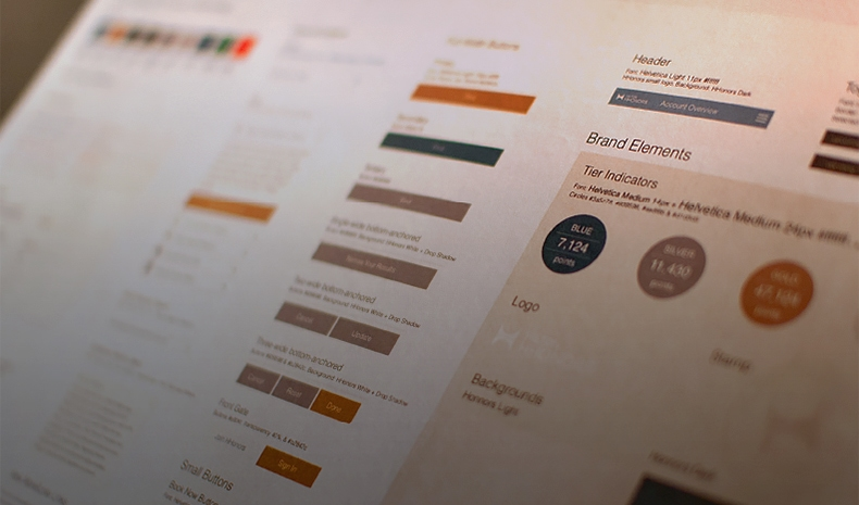 Photo of a sheet of paper showing certain brand colors, fonts and graphic treatments for the Hilton Honors website
