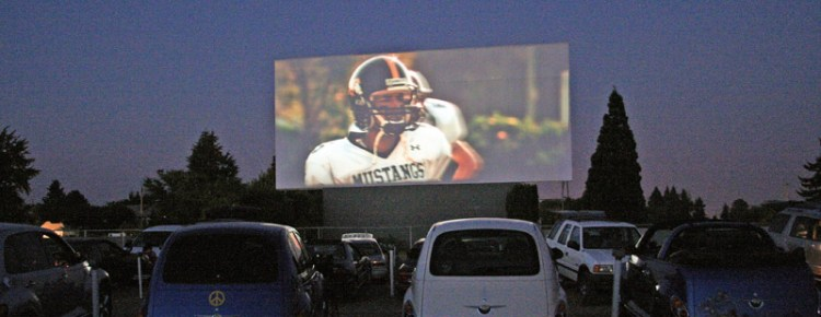 Cars at a drive-in with a football player on the screen