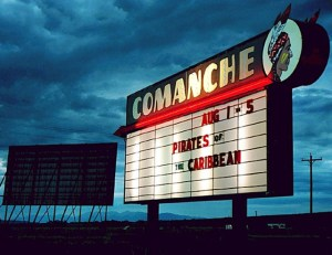 Comanche Drive-in marquee at twilight with screen in background