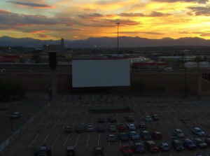 cars and a drive-in screen at twilight