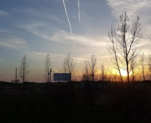 Drive-In screen at sunset with two contrails in the sky
