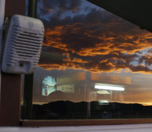 Concession stand window reflecting sunset clouds