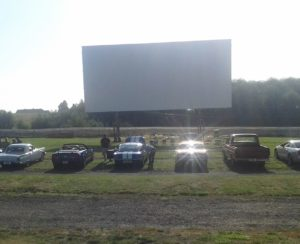 Drive-in screen with a line of cars in front