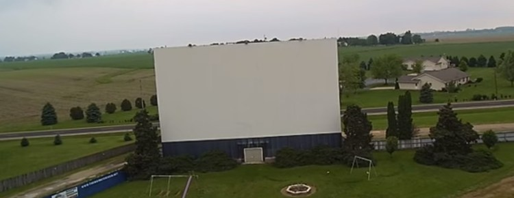 The screen of the Midway Drive-In with playground equipment in front