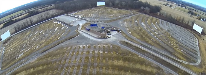 Aerial view of three drive-in screens with the booth in the center