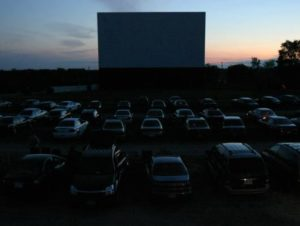Cars lined up in front of the drive-in screen at twilight