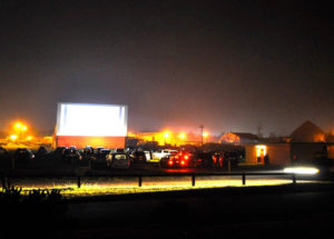 Lit drive-in at night with cars, the screen, and the concession stand