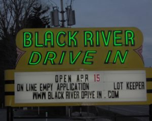 Black River Drive-In lit sign at twilight