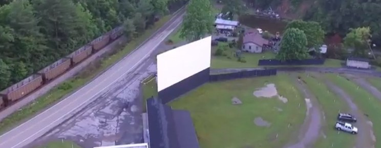 Aerial view of the Central Drive-In screen with a train passing across the highway
