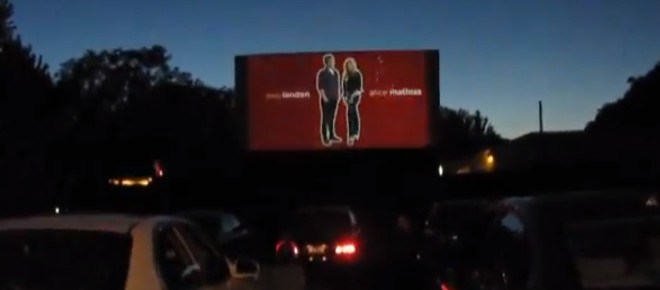 Cars watching a drive-in screen at dusk