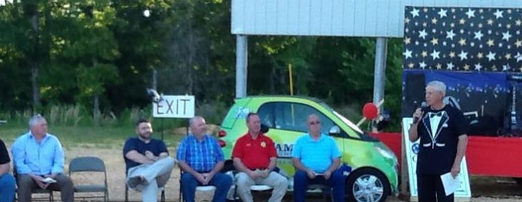 A small group sitting in front of a small drive-in movie screen