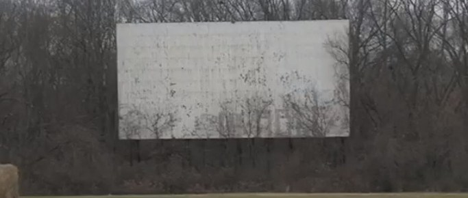 Old North Drive-In screen, surrounded by trees