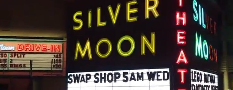 Neon-lit signs for the Silver Moon Drive-In at night