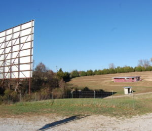 Grassy field with screen in foreground and projector building in back