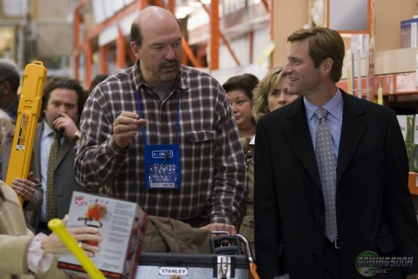 Aaron Eckhart has hypnotized John Carroll Lynch with his dimple into thinking that they're having a drink together.